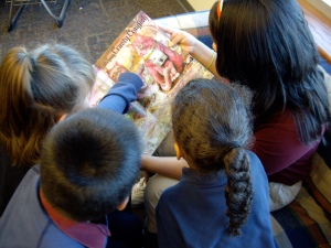 """Middle school student reading """"Anamalia"""" to 1st graders."""